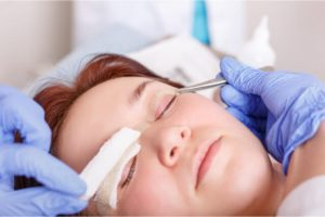 The plastic surgeon applies a bandage to the patient's eyelids after a blepharoplasty operation.