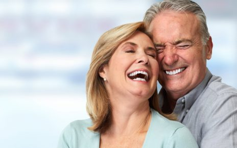 couple smiling after a dental implant procedure