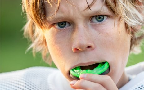 The young athlete wears a protective device for his mouth.